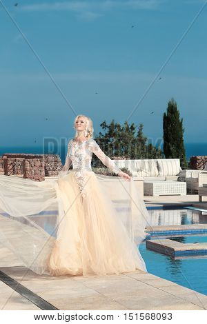 Beauty Portrait Of Gorgeous Bride In Wedding Dress With Blowing Skirt Walking Near Swimming Pool Ove