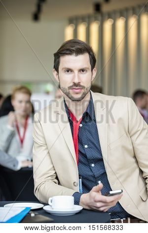 Portrait of confident businessman holding smart phone while sitting at convention center