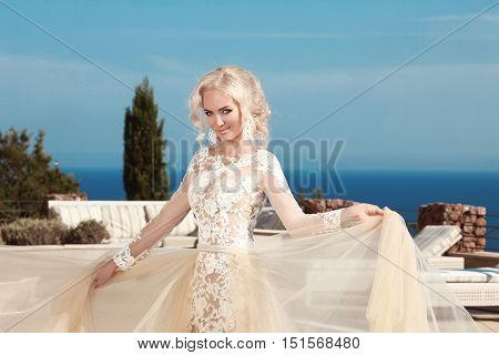 Beautiful Smiling Bride Dressed In Elegance White Wedding Dress Over Sea And Blue Sky, Outdoor Portr