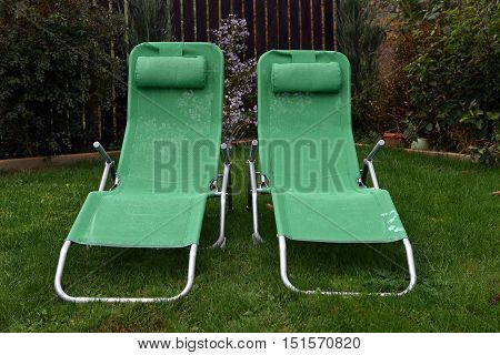 Green Deck Chairs In The Garden.