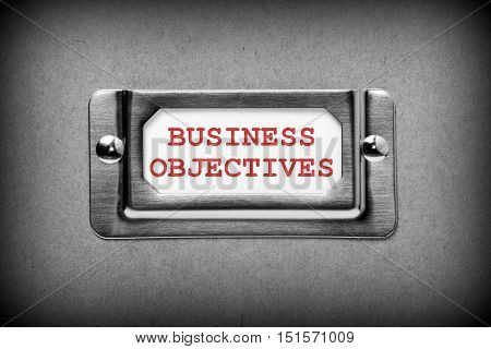 Filing cabinet drawer label with the words Business Objectives in red text as a reminder to include your desired outcomes at the planning stage