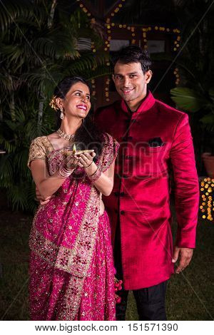 Indian young Woman holding a diya and husband standing behind, indian young couple celebrating diwali with diya in hand