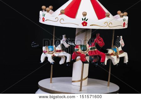 Old Toy wooden carousel on a black background