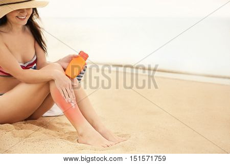 Young woman with red skin applying sun protective lotion on body at the beach