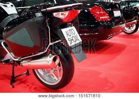 Black shiny bike for cortege, car are on red carpet in exhibition, back view