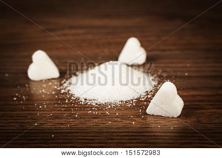 Sugar and sugar lumps form of heart on a wooden surface