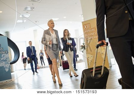 Business people pulling luggage while walking in convention center