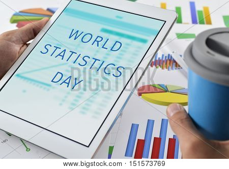 closeup of a young caucasian man at his office desk full of graphs and charts with a tablet computer in his hand with the text world statistics day in its screen