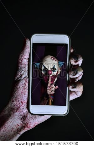 closeup of a scary and bloody hand holding a smartphone with a picture of a scary evil clown asking for silence in its screen