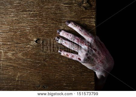 closeup of a scary and bloody hand popping up from a rustic wooden surface, with a negative space at his left