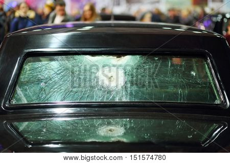 Rear black car window with traces of shots at exhibition, shallow dof, crowd out of focus