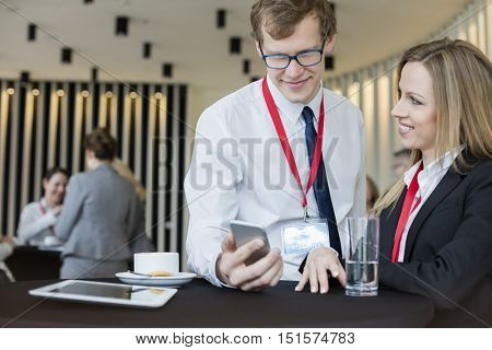 Businesswoman looking at colleague using smart phone during coffee break at convention center