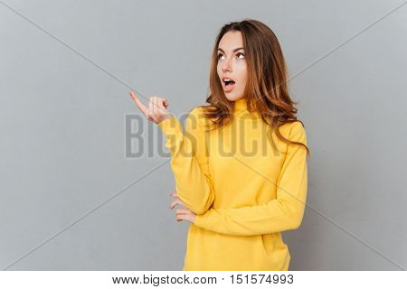 Young amazed woman in yellow sweater pointing finger away over gray backgorund