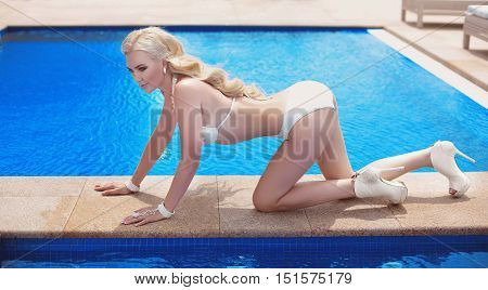 Beautiful Sexy Woman In White Swimsuit, Blond Model Tanned And Lying On Border Of Infinity Swimming