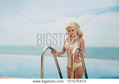 Beautiful Elegant Blond Woman, Bikini Model With Long Blonde Wavy Hair Style Wearing In Fashion Swim