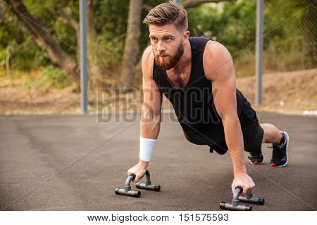 Muscular fitness man doing push-ups and using sports equipment outdoors