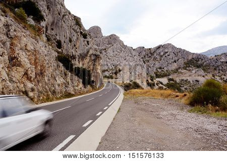 Car drives on winding mountain road asphalt highway with beautiful landscape on cloudy sky