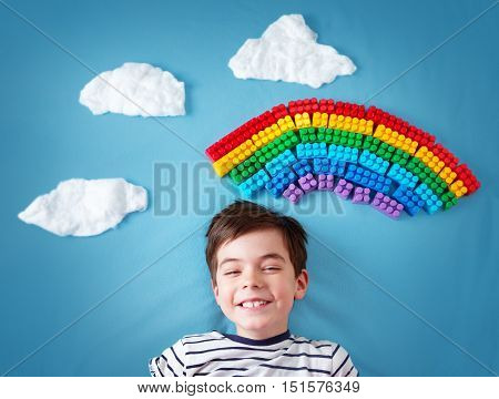 Child lying on blue blanket with rainbow and clouds