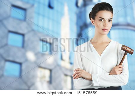Beautiful woman with judge gavel on blurred city building background. Justice concept.