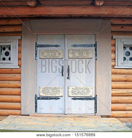 Wooden decorated doorway in timbered russian style house, square toned image