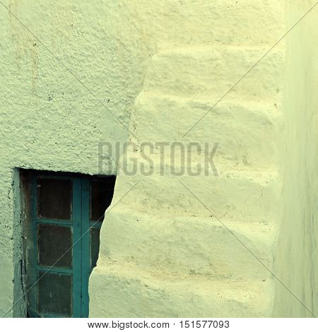The window and old white stairs of Santorini traditional house, Oia, Greece. Square toned image, instagram effect