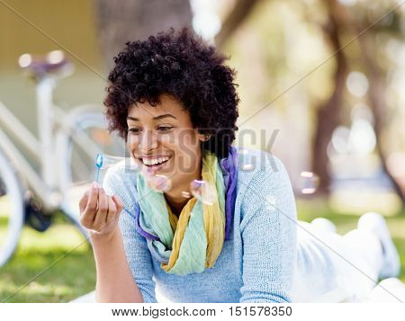 Beautiful woman blowing bubbles in park