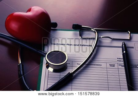 cardiologist stethoscope on paper insurance and heart shape