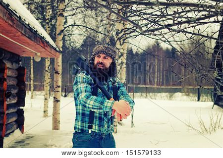 beard man in winter with axe outdoor
