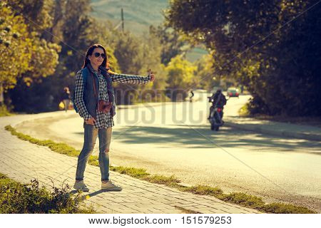 Girl wearing backpack holding map hitch hiking.