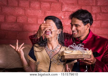 Indian husband surprising wife with a gift on diwali or anniversary or birthday, surprise gift concept and indian people or couple