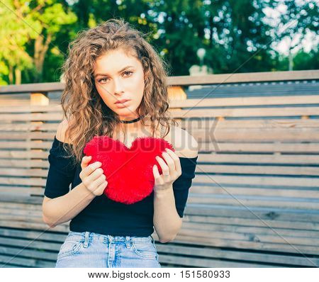 Love sadness and loneliness. Beautiful long-haired girl in sad loneliness summer evening. She is holding a big red heart. Broken heart. Warm color.