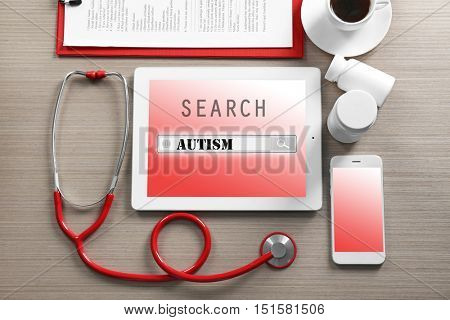 Red stethoscope with tablet and accessories on wooden table. Children autism concept