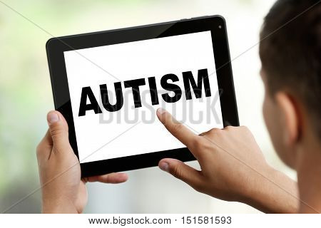 Children autism concept. Young man with tablet on blurred background