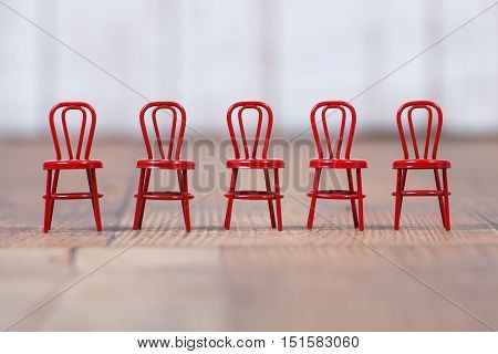 Red metal chairs in a line on wooden floor