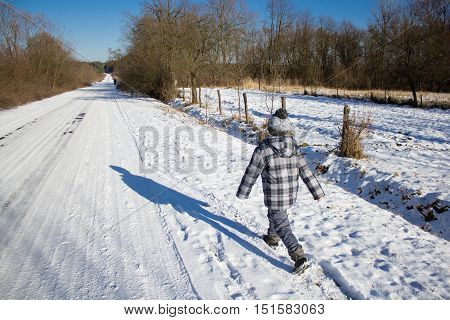 Boy goes quickly through the snow on the roadside