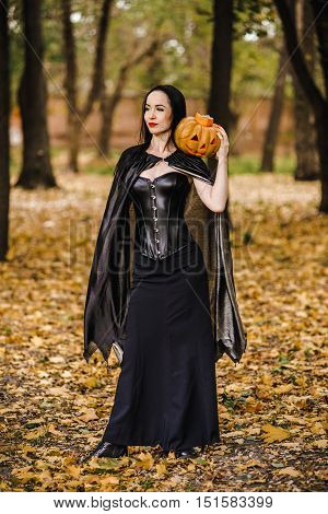 Young witch in the autumn forest. Girl with a pumpkin in black clothes in the park