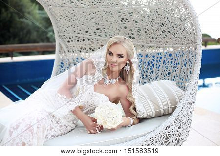 Beautiful Bride Portrait Holding Wedding Bouquet Posing In Lace Mermaid Dress. Makeup. Wavy Hairstyl