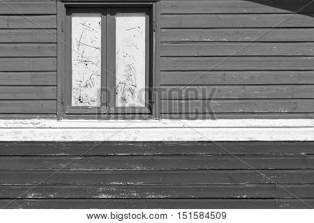 fragment of an old wall of the house from wooden boards with one big window monochrome gray tone