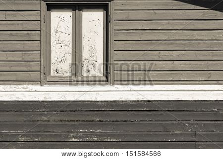 fragment of an old wall of the house from wooden boards with one big window beige tone sepia
