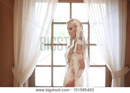 Elegant Bride Wedding Portrait. Fashion White Lace Veil. Beautiful Blond Model Posing By The Window
