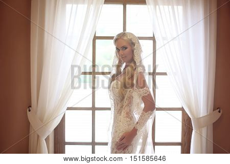 Elegant Bride Wedding Portrait. Fashion White Lace Veil. Beautiful Blond Model Posing By The Window