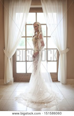 Beautiful Bride In Wedding Dress With Long Bridal Veil Posing By Wooden Window Frame With White Curt