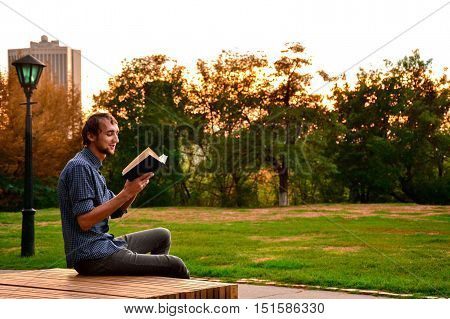 Guy sitting on a bench in the park reading book