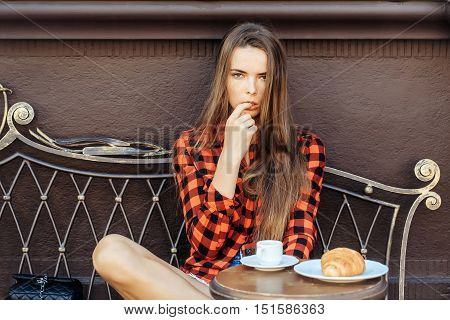 Sexy girl pretty slim model in red checkered shirt and shorts licks finger on vintage coach in coffee cafe