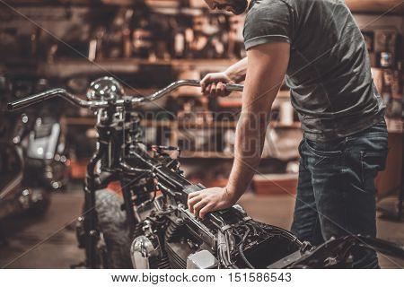 Man examining motorcycle. Close-up of young man examining motorcycle in repair shop