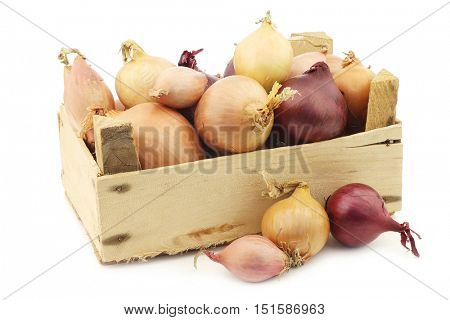 mixed onions in a wooden box on a white background