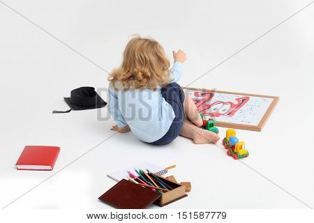 Little boy child in blue shirt playing with drawing school board plastic toy car near box with colored pencils isolated on white background