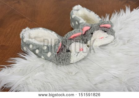 pair of bunny slippers on white fur rug and wood floor