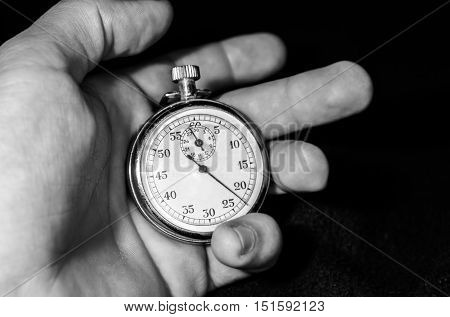 Stopwatch in hand, backgraund black, and white.