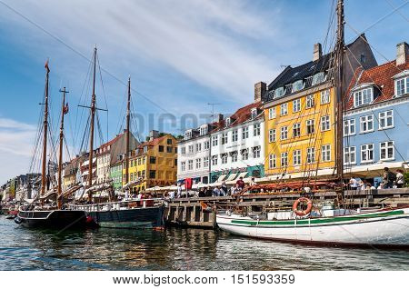 Copenhagen Denmark - August 5 2010: Nyhaven Waterside. Colourful houses by the harborside of this historic district in Copenhagen with sailing boats mored in the foreground on August 5 2010.